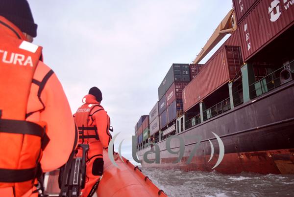 Momento que que la tripulación de Prefectura se acerca al buque containero