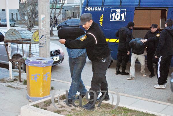 Efectivos policiales trasladan a los detenidos en el operativo antidrogas